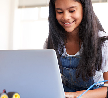 young girl facing computer