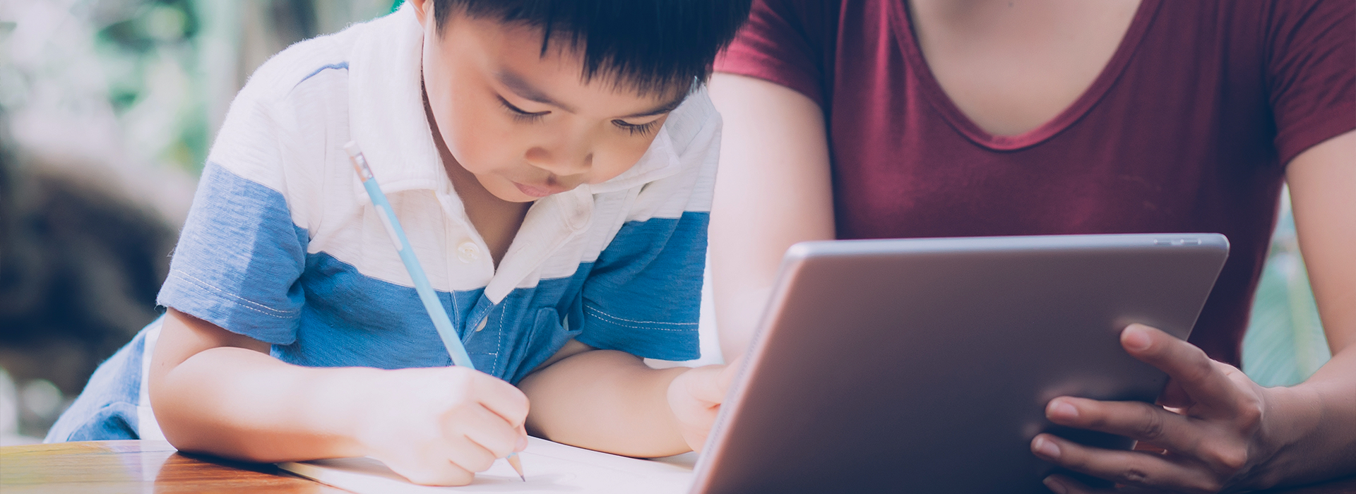 young boy drawing a picture from an ipad screen